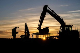 The setting sun silhouetting diggers and operatives working on Daedalus Common
