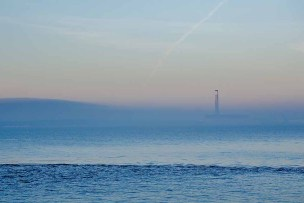 Fawley power station partly obscured by a bank of fog photographed from the Meon Shore at Hill Head