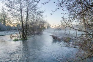A flooded River Meon flows through the Meon Valley Hampshire near Droxford