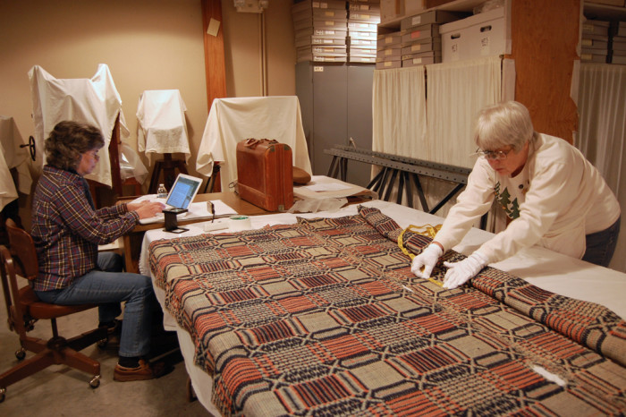 Marty Benson (left) and Laura Redford studying a coverlet from the Shiloh Museum collection.