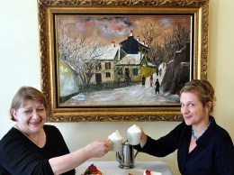 Birte, left, and Charlotte Andersen are the mother-daughter duo behind Andersen's Danish Restaurant and Bakery in Santa Barbara. The business was started by Birte and her late husband Alfred in 1976 and is now a downtown landmark. The painting is by Alfred. (Wendy Jensen / courtesy photo)