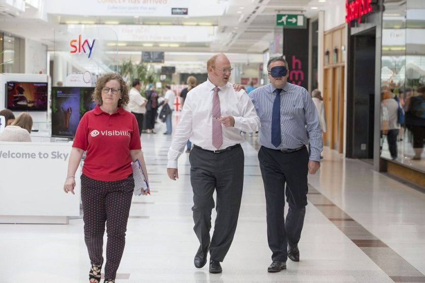 Shopping centre boss, Peter Beagley is blindfold and led through the mall by guest services manager, Bruce Harley and Visibility trainer, Anne Garry