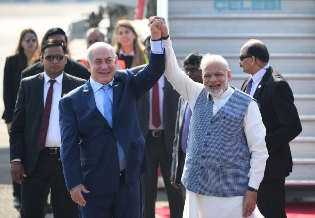 Indian Prime Minister Narendra Modi (R) and Israeli Prime Minister  Benjamin Netanyahu pose for photographers after Netanyahu arrived at the Air Force Station in New Delhi on January 14, 2018. / AFP PHOTO / PRAKASH SINGH