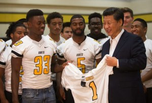 """Mushawn Knowles, left and Dionte Simon, both 17 and members of the football team,  present Chinese President Xi Jinping with a custom """"Xi"""" jersey in the gym during his visit at Lincoln High School in Tacoma on Wednesday, Sept. 23, 2015.  President Xi previously visited Lincoln High School in 1993 when he was a local government official in Tacoma's sister city of Fuzhou, China. On Wednesday, he toured the Boeing factory in Everett, visited Microsoft in Redmond, and returned to Lincoln High in Tacoma, causing traffic backups across the region.  (Lindsey Wasson / The Seattle Times)"""