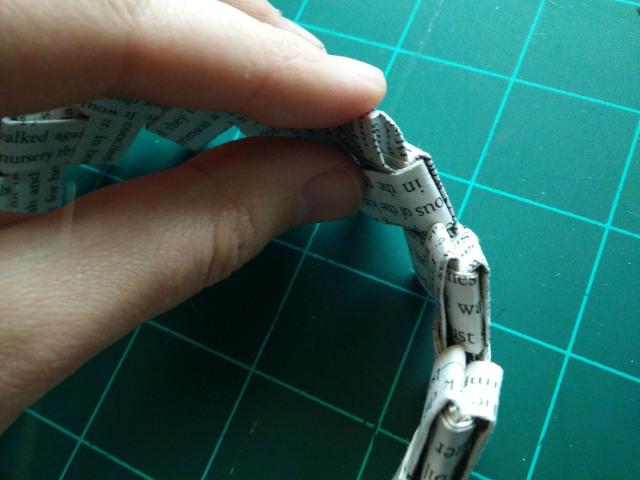 Pliez le dernier bout au milieu du papier plié, entre les deux boucles