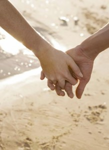 A couples holds hands on the beach finding love where they least expected it