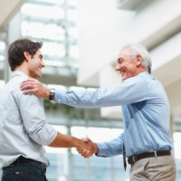 Business agreement - Senior and young male executives shaking hands at office