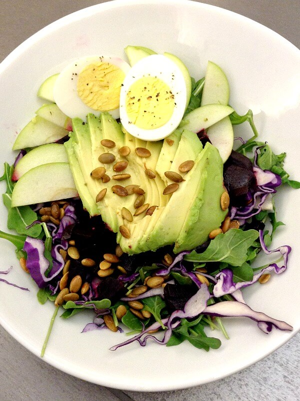 Whole30 compliant salad with arugula, purple cabbage, avocado, beets, pumpkin seeds, apples and hard-boiled egg from the cafe at Y2 Yoga in Charlotte.