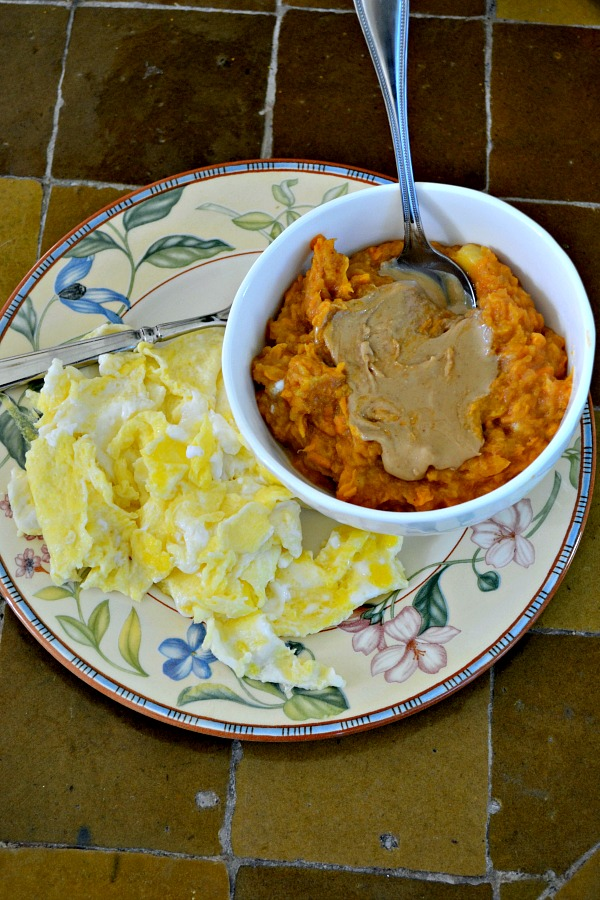 Mashed sweet potatoes with banana and coconut milk topped with cashew butter and served with two scrambled eggs