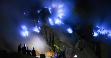 Silhouette of tourists looking into the blue fire a flow of liquid sulfur which has caught fire and burns with an blue flame. Cater of the Kawah Ijen volcano, Java, Indonesia. Pelita Borneo Tours