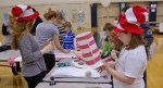 """Children make hats at the """"Cat in the Hat' table."""
