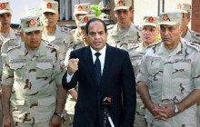 Egyptian President Abdel-Fattah el-Sissi, center, speaks in front of the state-run TV ahead of a military funeral for troops killed in an assault in the Sinai Peninsula, as he stands with army commanders in Cairo. (Photo: AP/MENA/Mohammed Samaha)