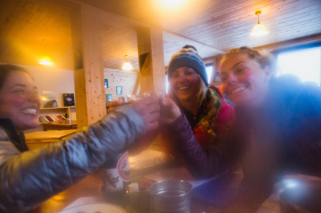 Maria DeBari, Liz Daley and Bibi Pekarek clink wine glasses at the Argentiere Refuge after a cold day of touring. My lens was frozen and fogged. Chamonix, France.