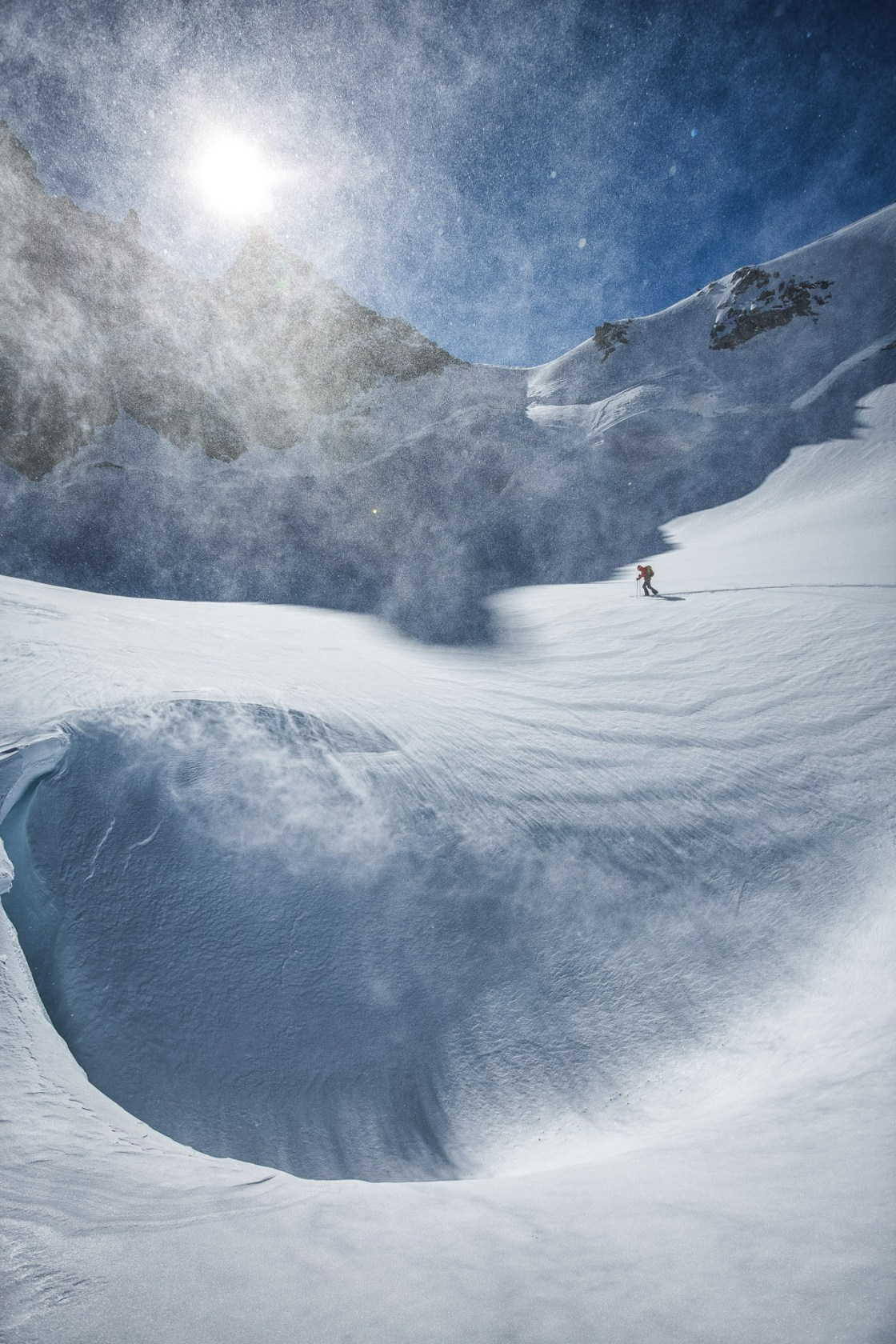 Liz Daley skins Glacier des Améthystes, Chamonix, France.  It was a bitter cold day with negative double-digits Fahrenheit temps. Liz is in diesel truck-mode, breaking trail with head down, hood up, and about to commit to a few hours in the shade. Powder that had been fresh the day before was scoured by wind overnight and so we worked to find sheltered riding while staying off of fresh, sensitive wind slabs. Eventually we made our way down the Switzerland side of the mountain, cooked by candlelight at a climbers hut, then toured out to Les Montets the following afternoon.