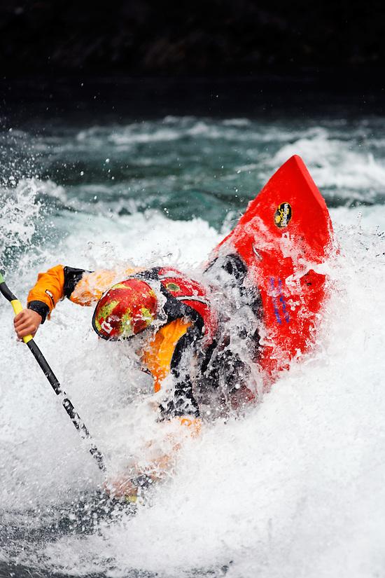 Andrew Jobe dives into a hole in a whitewater kayak on the Kananaskis River, Kananaskis County, Alberta, Canada (Brad Mitchell)