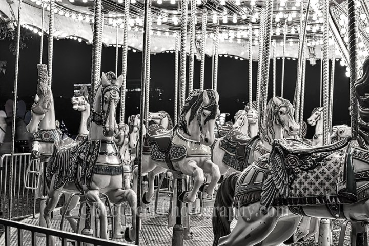 This is an image of the carousel horses at a amusement fair taken late at night after the last ride of the night in black and white which brings out that sort of haunting errie look almost like something a little surreal or something you would see in a  a twilight zone episode . (Tod Grubbs & Cynthia Hestand)