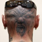 A man displays his tattoo