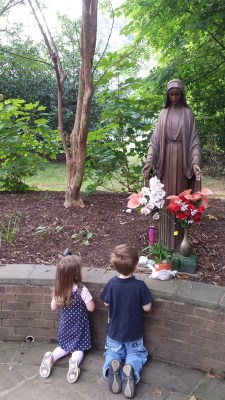 children kneeling before statue of Mary