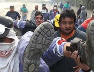 Obrero herido de bala en la pierna es socorrido por sus compañeros.
