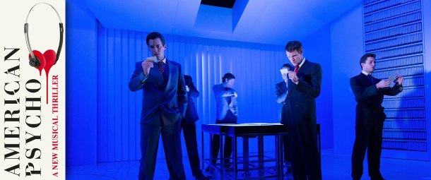 A scene from American Psycho the musical at the Almeida Theatre. The image shows Matt Smith in the lead role of Patrick Bateman and 5 other male members of the cast in an office scene. They are all suited and the set is highly stylised in electric blue with a single table whose surface top emits from within a bright white light.