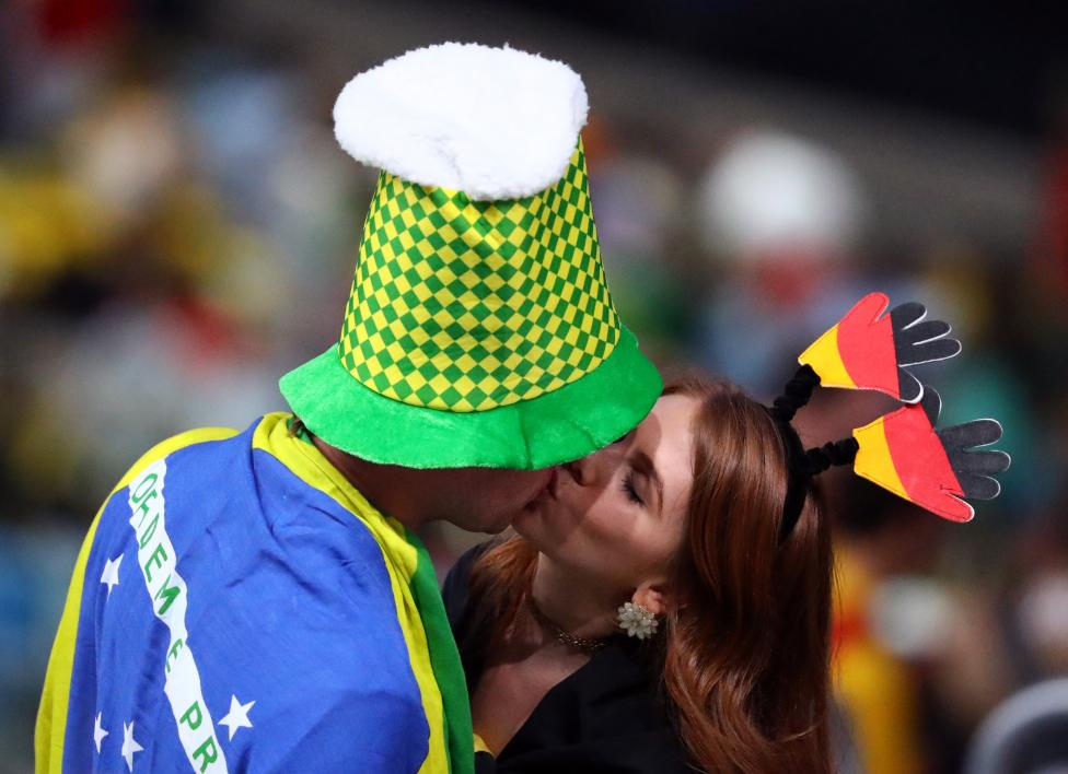 A man with a Brazilian flag kisses a woman dressed in the  German flag. REUTERS/Lucy Nicholson