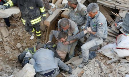 A man is rescued alive from the ruins following an earthquake in Amatrice, central Italy. REUTERS/Remo Casilli