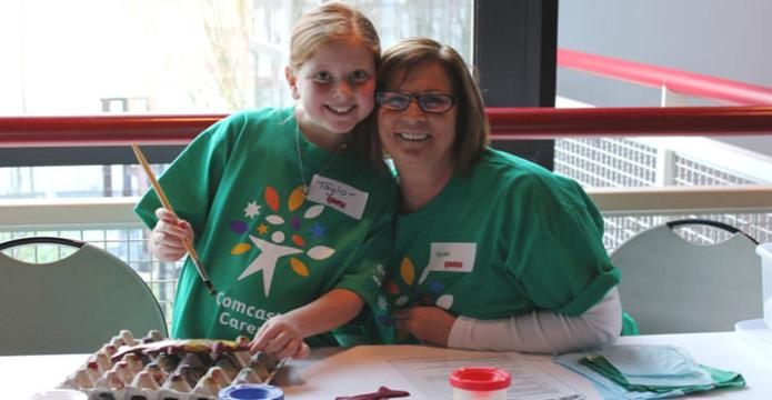 Comcast employee Vicki Klein and granddaughter Taylor Menard man the fish printing station at OMSI. Photo by Rosemarie Cordell.