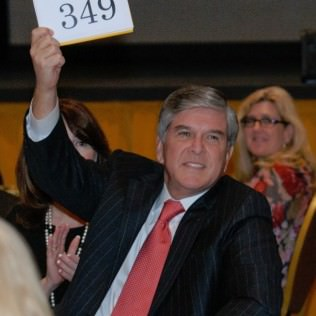 Senator Gordon Smith raises his paddle high for Lines for Life
