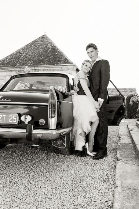 Mariés près d'une voiture ancienne
