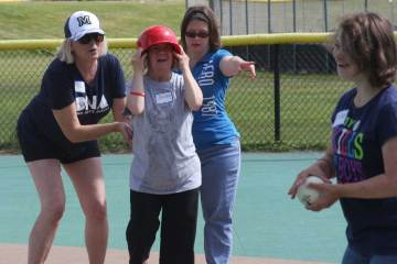 Getting a little help while playing softball with corporate volunteers.