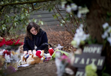 Dilma Steiner, of Newtown, Conn., visits a sidewalk memorial for the Sandy Hook Elementary School shooting victims, Sunday, Dec. 16, 2012, in Newtown, Conn. (David Goldman/AP)