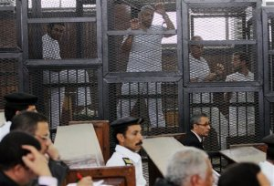 Al-Jazeera's acting bureau chief Mohammed Fahmy, a Canadian-Egyptian, center, and Australian correspondent Peter Greste, center right, appear in a defendant cage along with other defendants during a trial on terrorism charges in Cairo, Egypt, Thursday, May 22, 2014. (AP Photo/Ahmed Gamil)