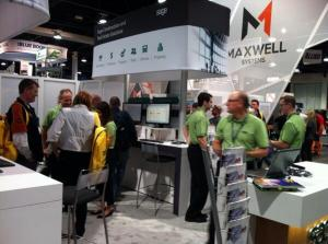 Many people stand inside a trade show booth at the World of Concrete exhibition in Las Vegas. The booth staff, employees of Sage software, are wearing sage green shirts and black pants.