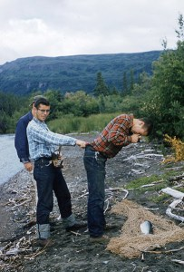 """Biologists find the perfect balance for photographing salmon near the weir site in July 1959. """"Theodore Merrell Collection,"""" Records of Katmai National Park and Preserve, Anchorage, Alaska."""