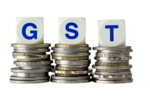 Stacks of coins with the letters GST isolated on white background