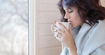 Young beautiful brunette woman covered in blanket with cup of coffee sitting home by the window. Winter snow landscape view. Lazy day off concept