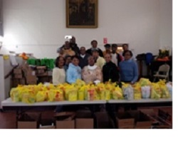 Volunteers with pastors Willie J. Keaton (third row, second from left) of Claremont-Lafayette and Gloria Tate (front row, center) of Teaneck Presbyterian with the turkey dinners to be donated
