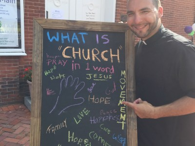 Rev. Fernando Rodriguez Quinones displays a sign with responses from Peach Festival attendees
