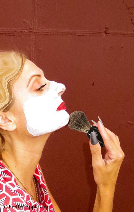 woman shaving her beard with shaving brush