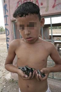 Un niño carga casquillos después de una balacera. en Sinaloa. Foto: Juan Carlos Cruz