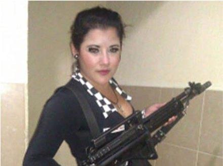 Una de las sexoservidoras que posaron con las armas de los policías. Foto: Especial