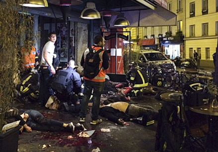 Un hombre llora mientras coloca flores en frente de la cafetería Carillon, en París, tras los atentados del viernes. Foto: AP