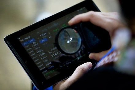 Una mujer revisa los indicadores financieros en China. Foto: AP / Andy Wong