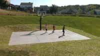There are three kids playing basketball on their backyard ...