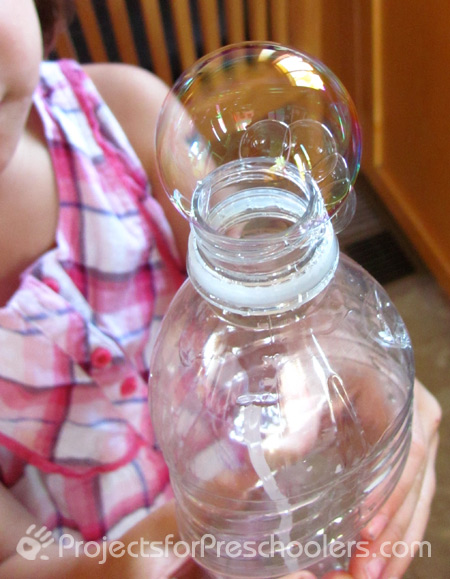 blowing bubbles with a plastic bottle