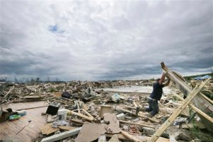 In this  April 30, 2014 file photo, Dustin Shaw lifts debris as he searches through what is left of his sister's house in Vilonia, Ark. Forecasters who are troubled by the high death count from twisters in recent years say they must find better ways to communicate if the public is going to behave appropriately as bad weather approaches. (AP Photo/Danny Johnston, File)