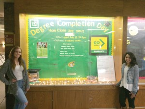 Photo by David Saveanu | Student Services employees Abbi Nowak and Melissa Rodriguez in front of the Degree Completion Day display case in the X-wing.