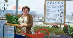 Photo by Lindsay Cox |  Humanities faculty member Eva Ginsburg poses with her flowery finds at the Parkland plant sale.
