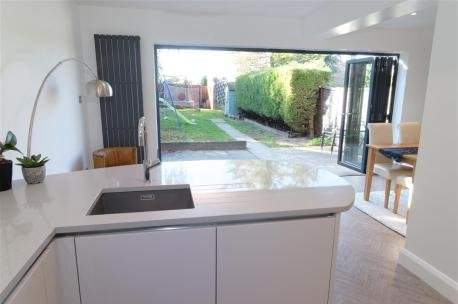High Gloss Taupe Kitchen with Blanco Sink and Silestone worktops Alumino Nube / bi-fold doors
