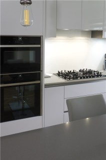 Handle less Polar white kitchen with Gris expo surfaces